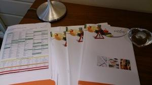 Tre tjocka mappar med recept, genomgång av testet och provsvaren.